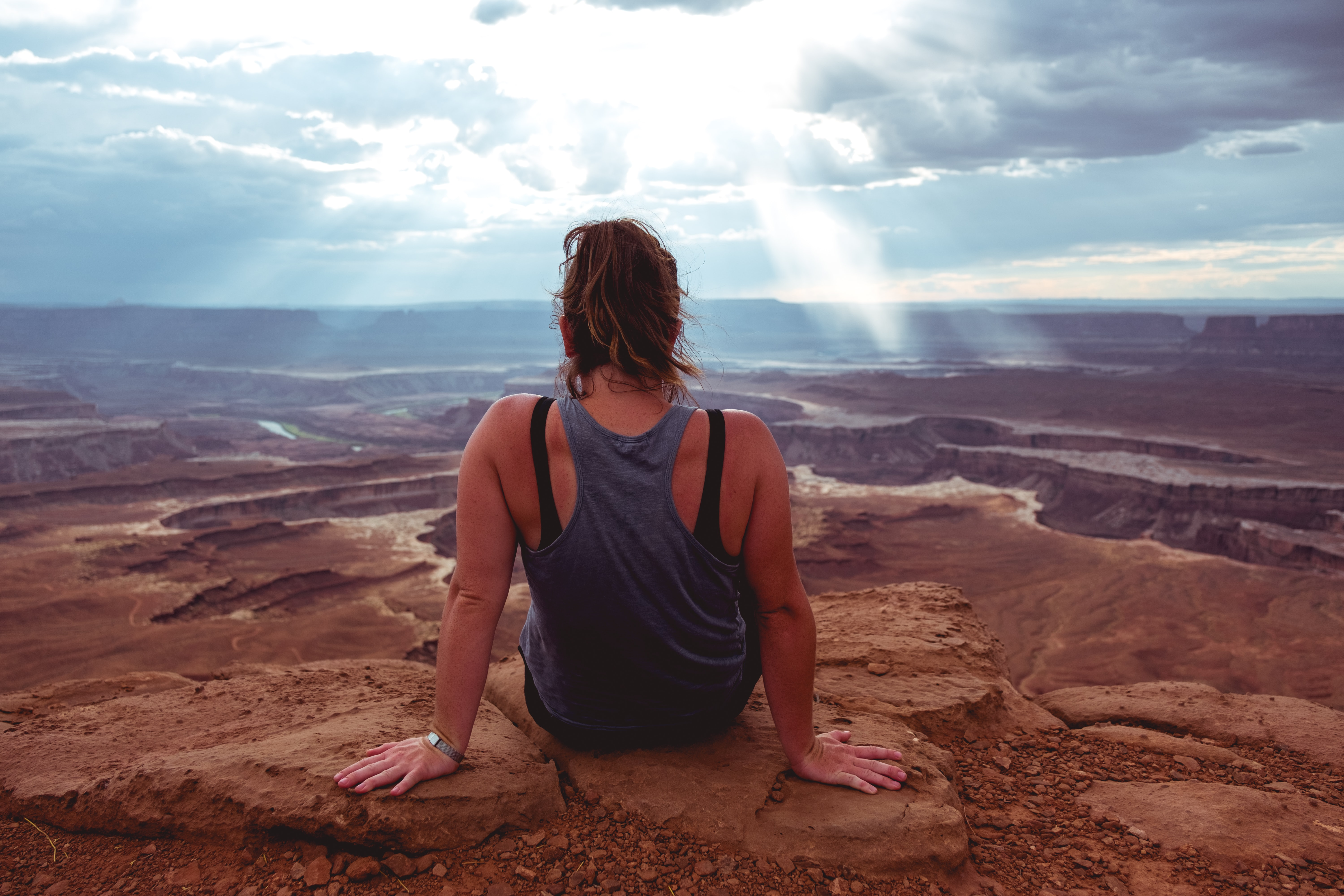 woman sitting on cliff at daytime