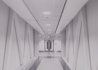 person taking photo of white and gray hallway