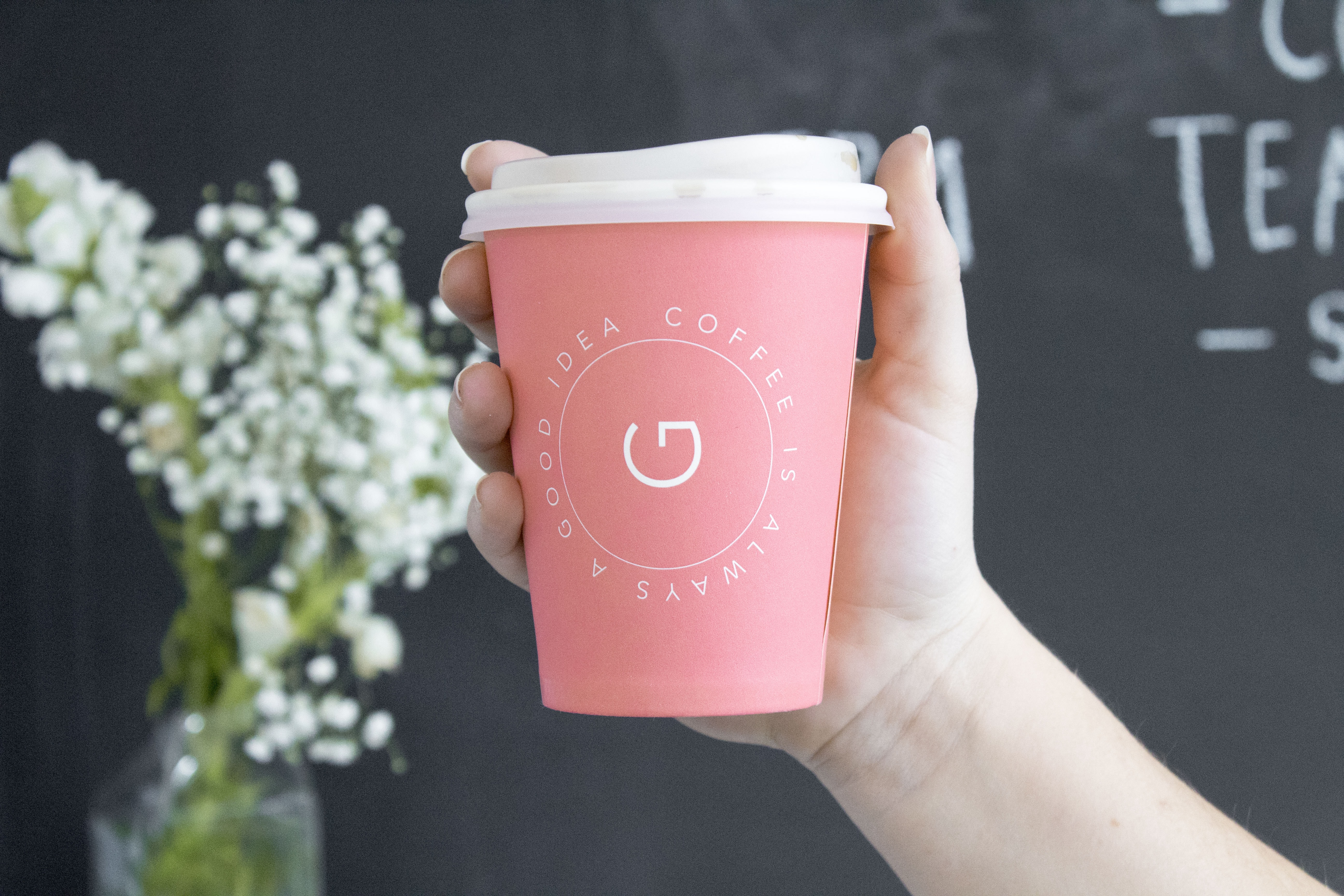 person holding pink and white disposable coffee cup
