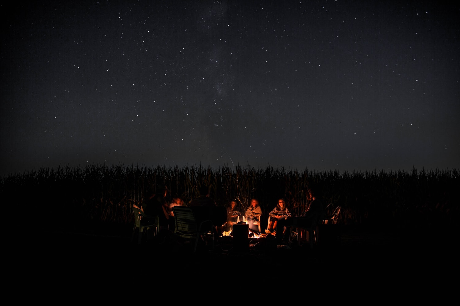 Group of people is having a campfire underneath the beautiful stars