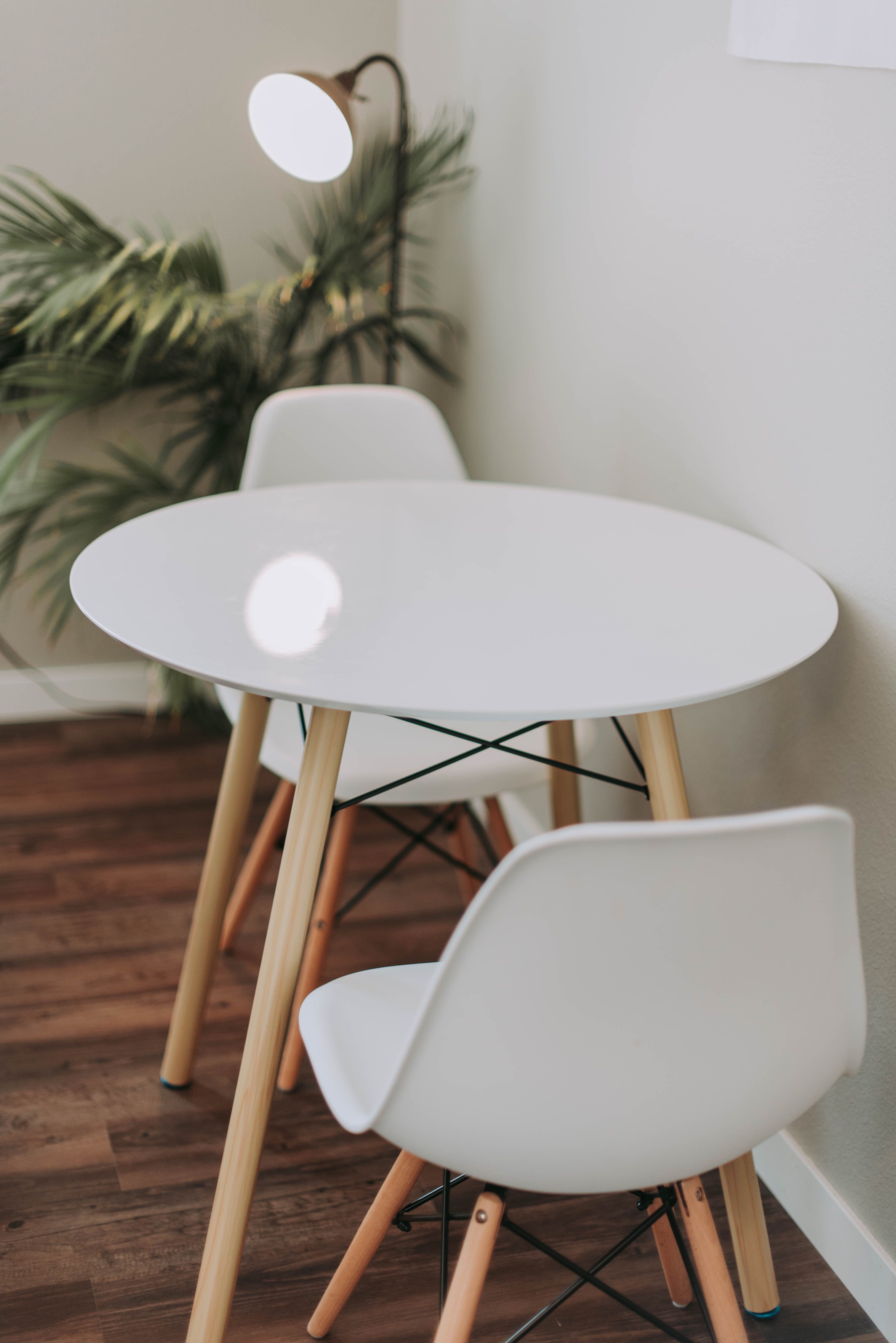 round white wooden 3-piece bistro set beside floor lamp
