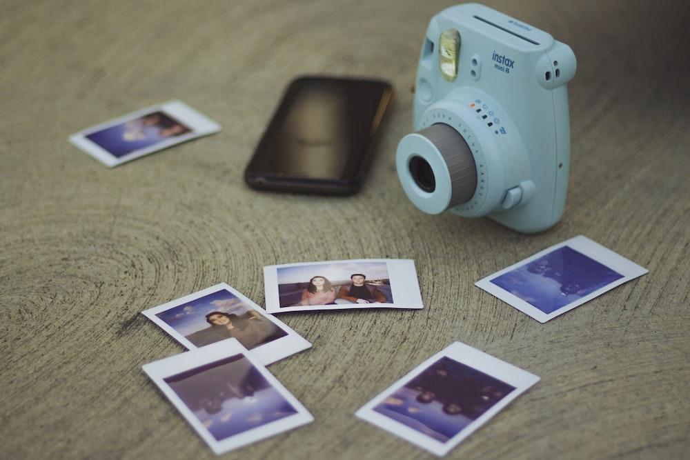 white Fujifilm Instax mini camera beside printed photos