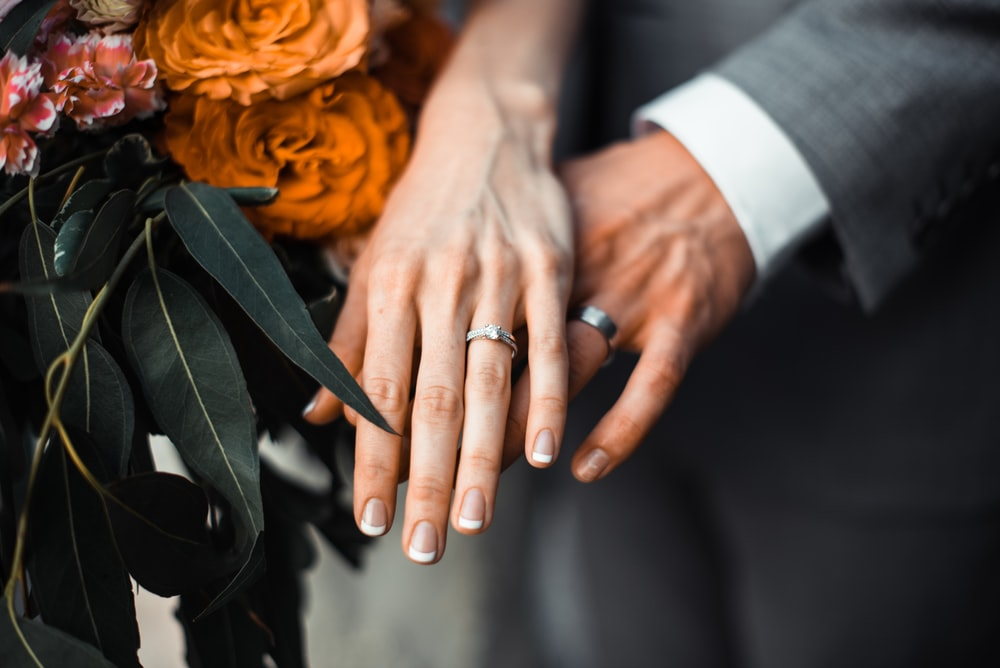 man and woman wearing silver-colored rings