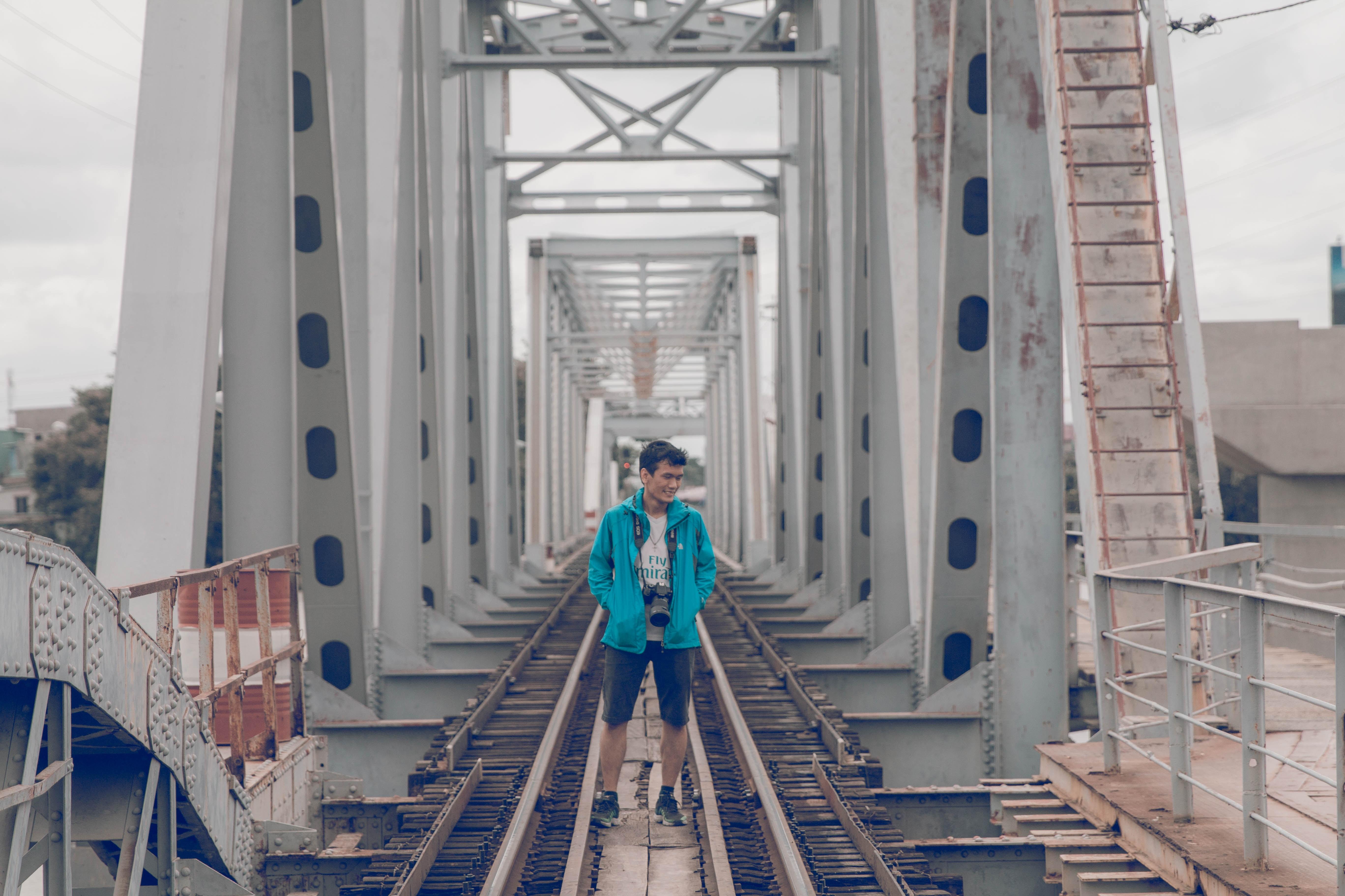 man wearing jacket standing on gray train bridge