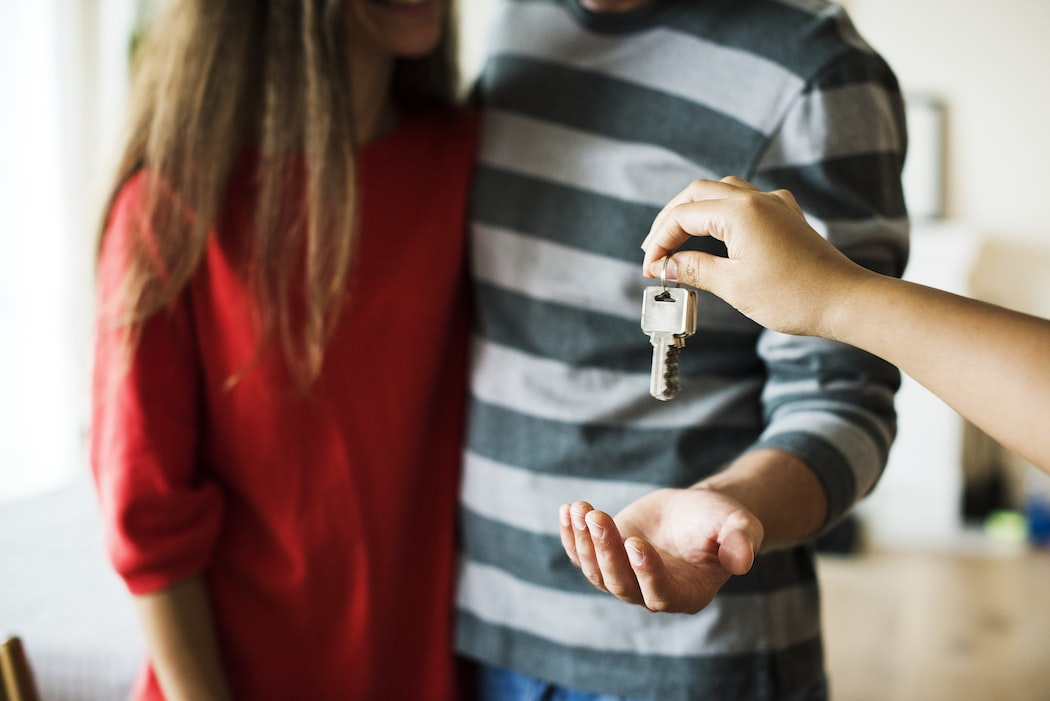 Man reaches out hand for key while embracing woman | KeyRealtySchool.com