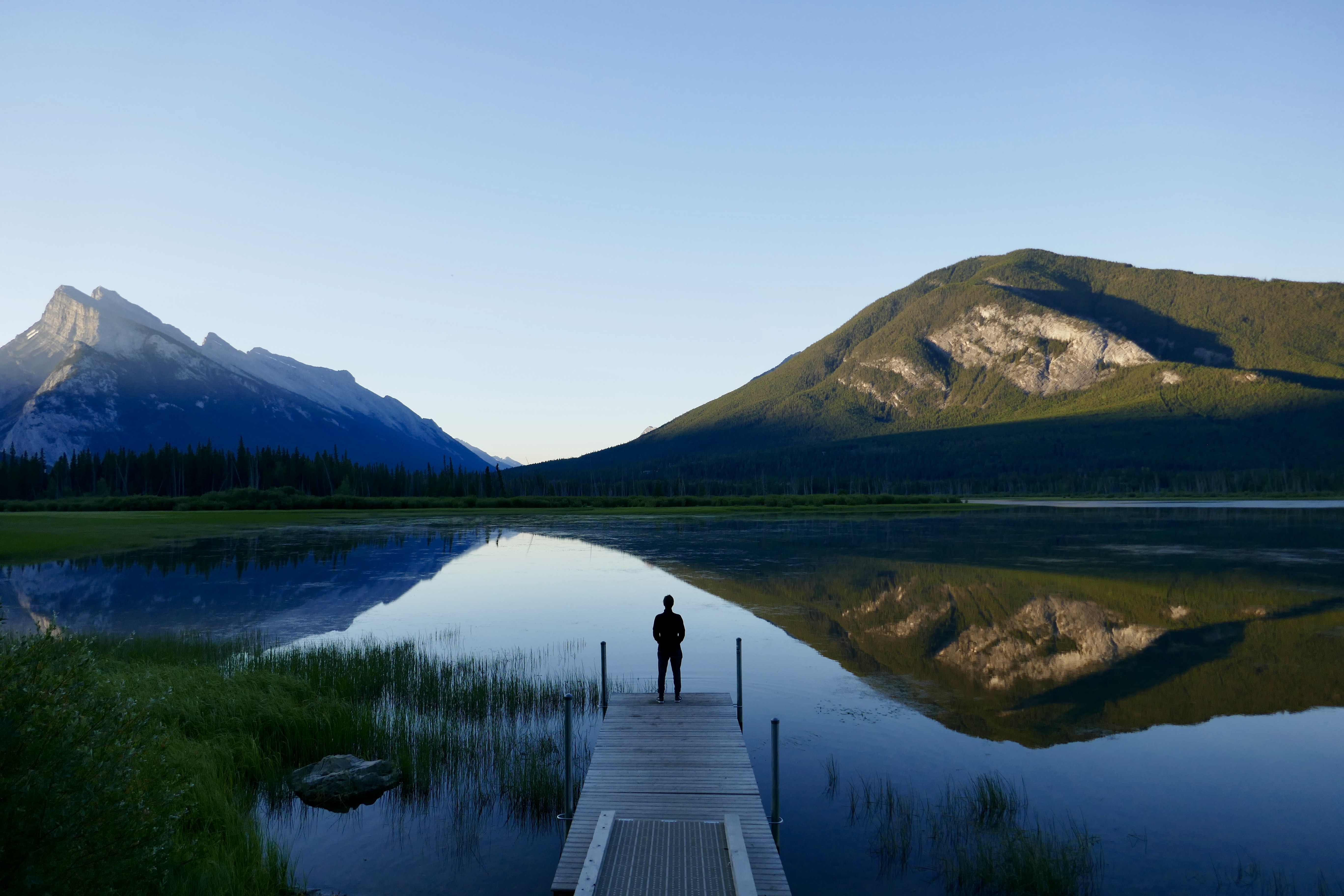 man standing on dock facing body of water and mountains during daytime
