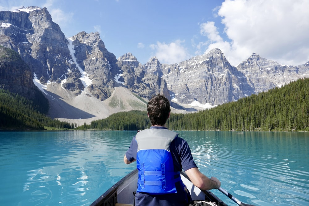 man kayaking near mountain and forest