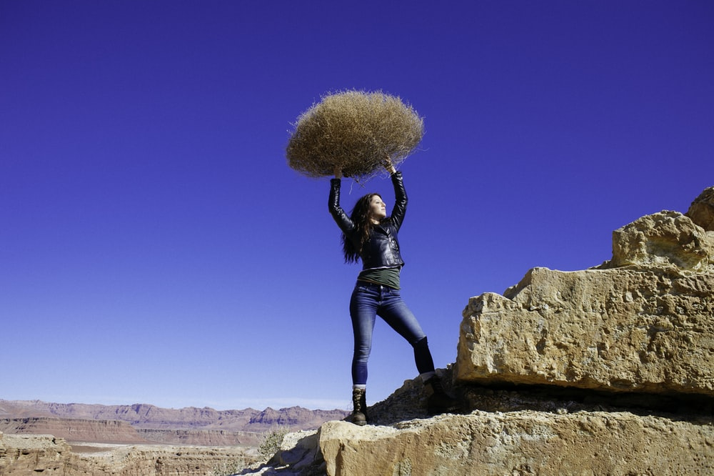 woman standing on rock formation while carrying hay during daytime