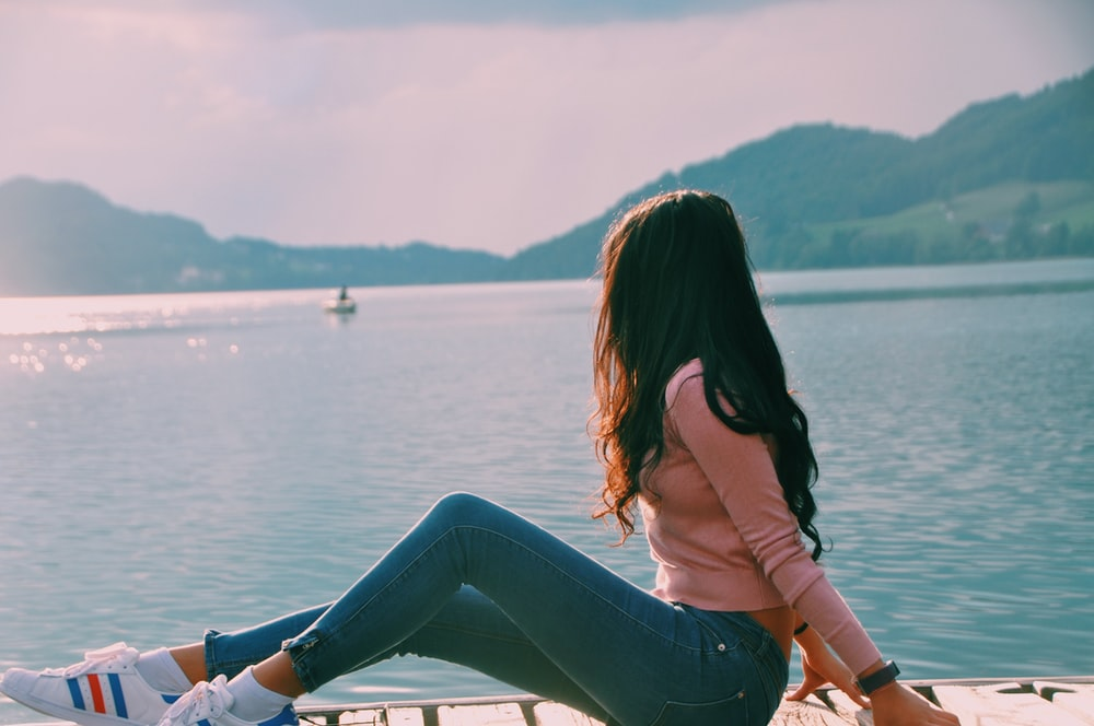 woman sitting on beach dock while looking on boat