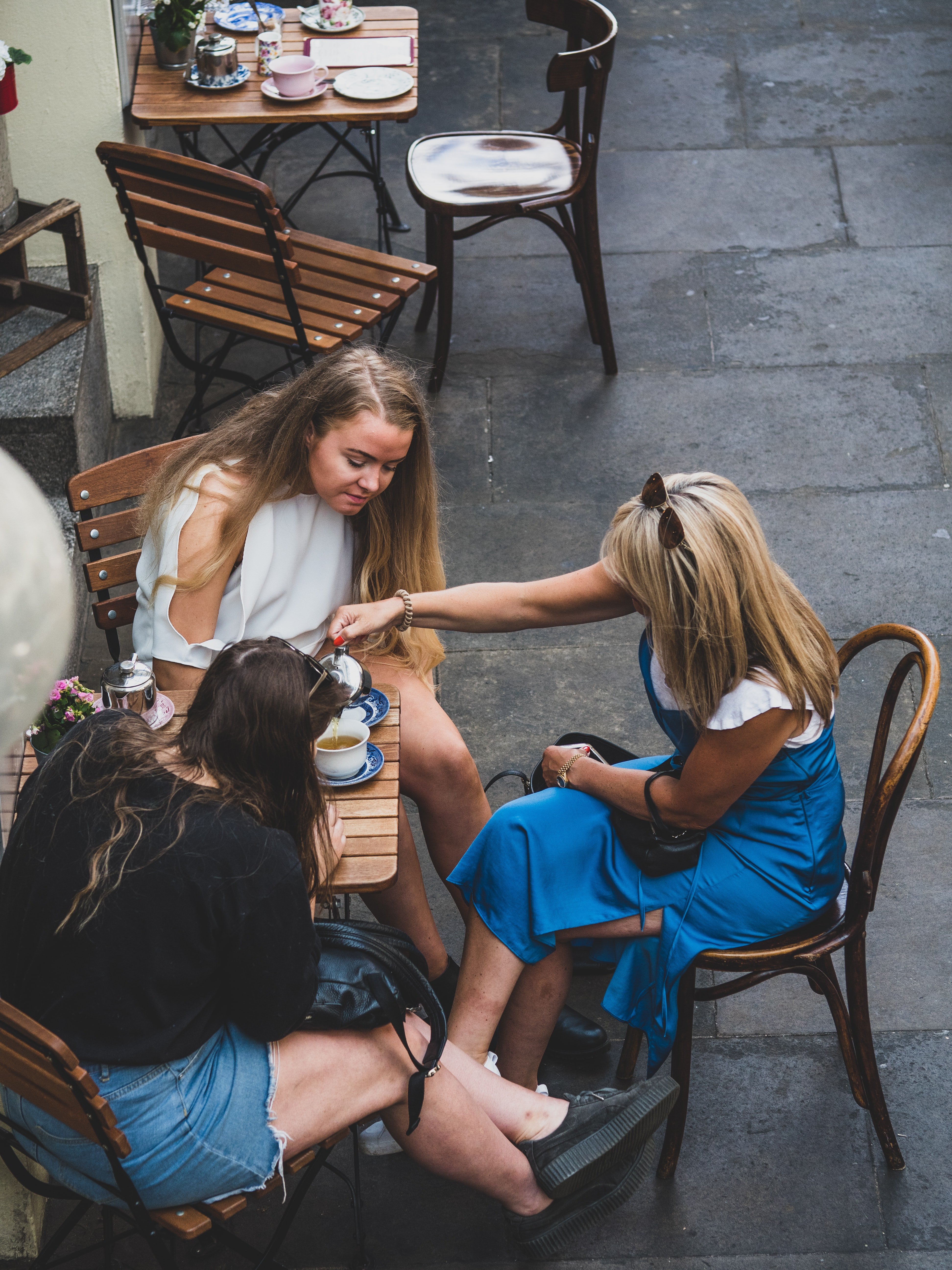 three woman drinking coffee together with sitting