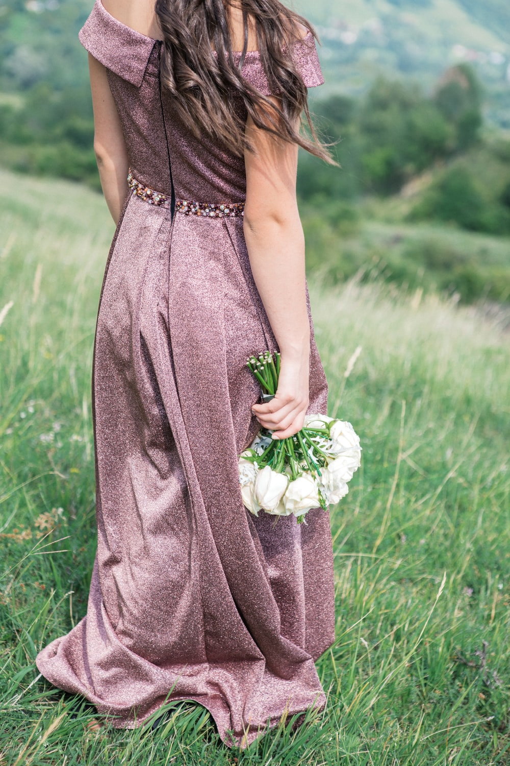 woman standing on grass fields holding bouquet of white flowers