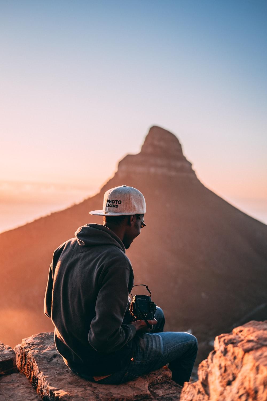 man sitting on stone facing mountain