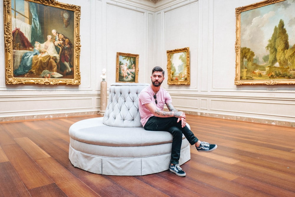 man sitting on white couch inside art room