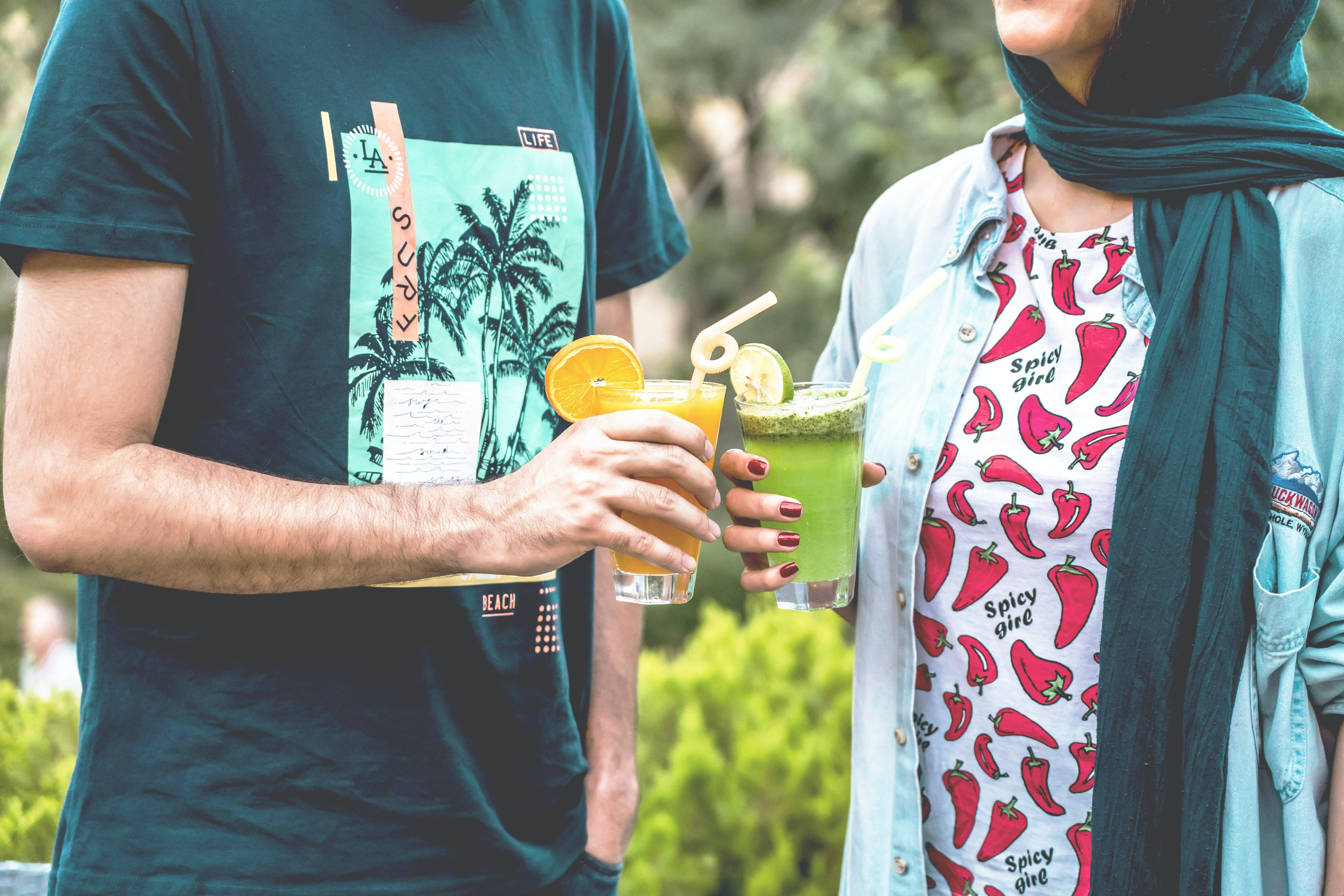 man and woman standing while holding drinking glasses during daytime
