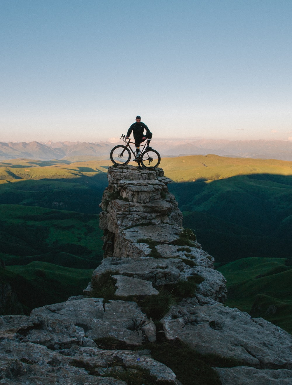 man holding bike while standing on gray mountain
