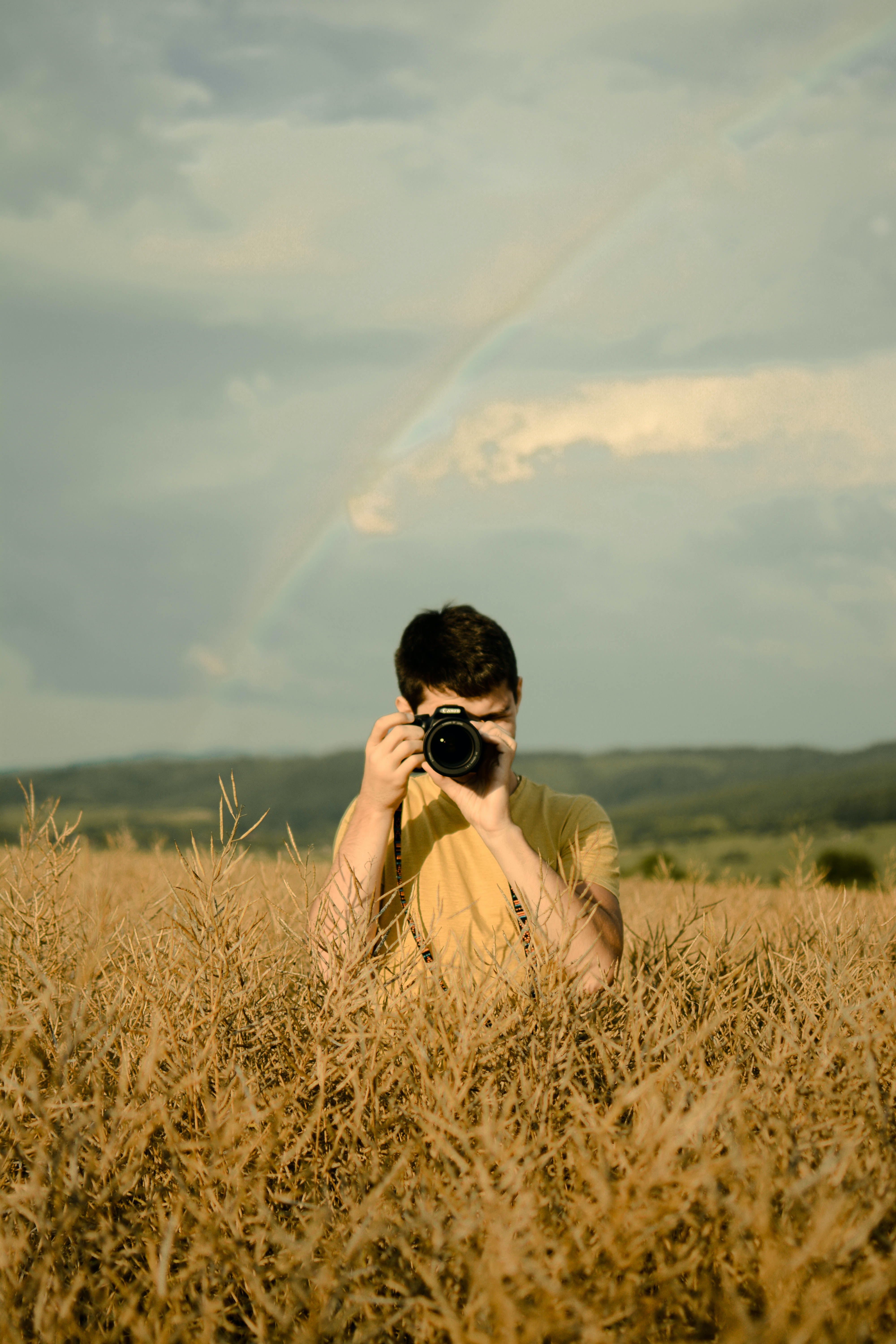person using DSLR camera in middle of grass field