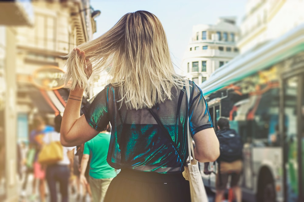 selective focus photography of woman waving her hair on crowded place