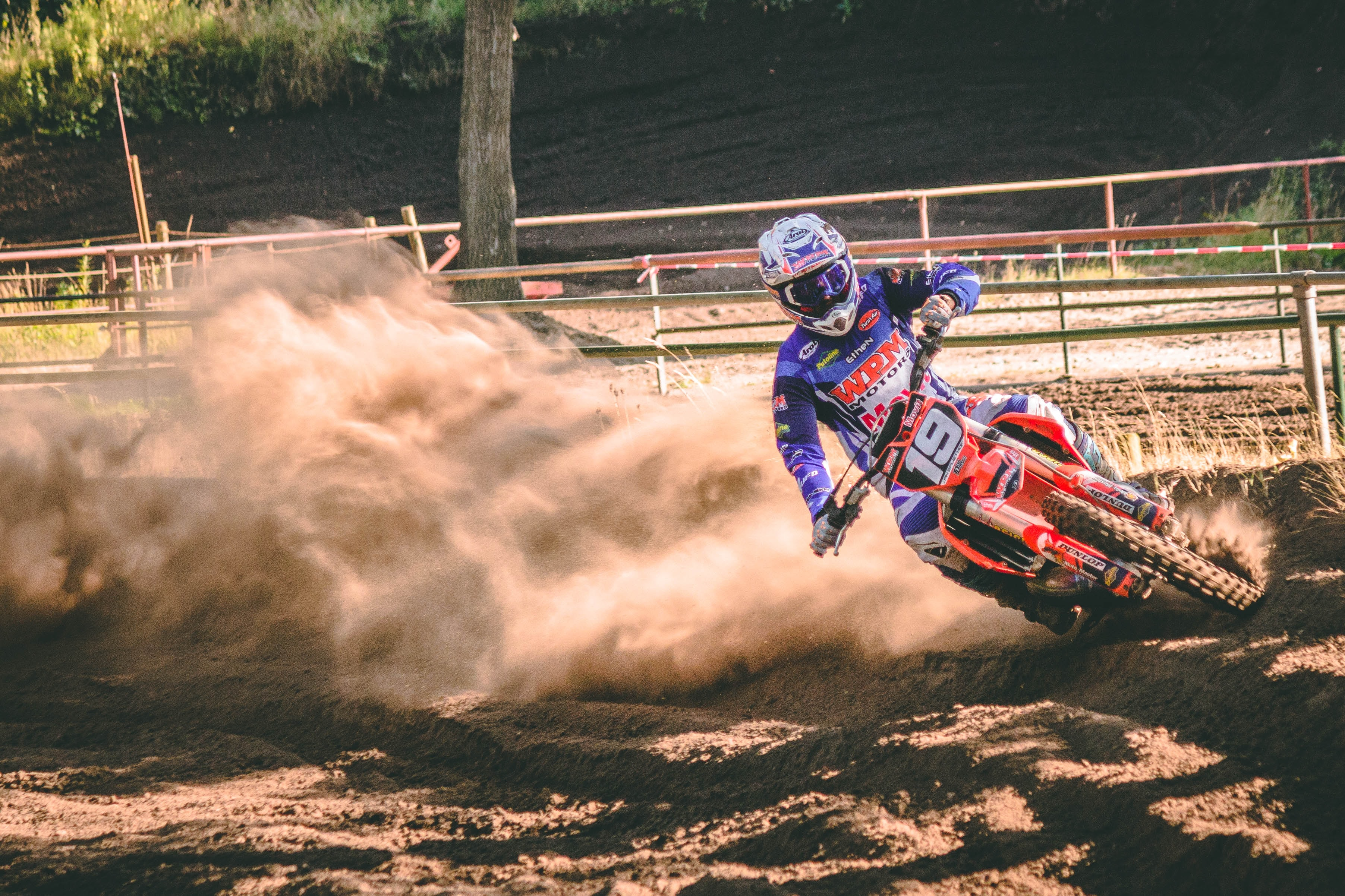 person riding on motocross dirt bike drifts on race track