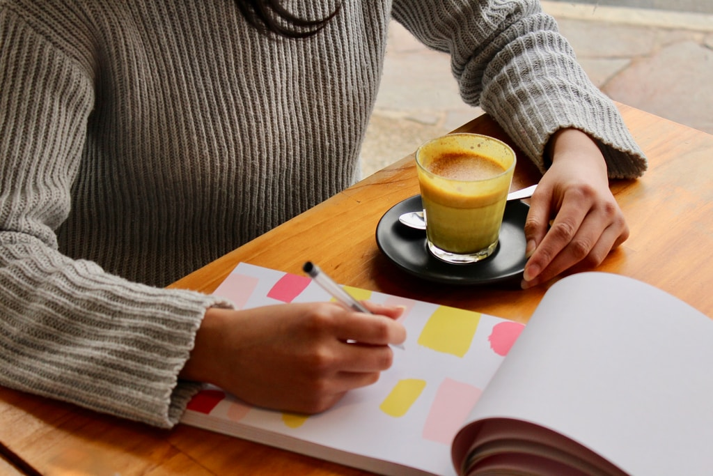 person holding pen with coffee on table