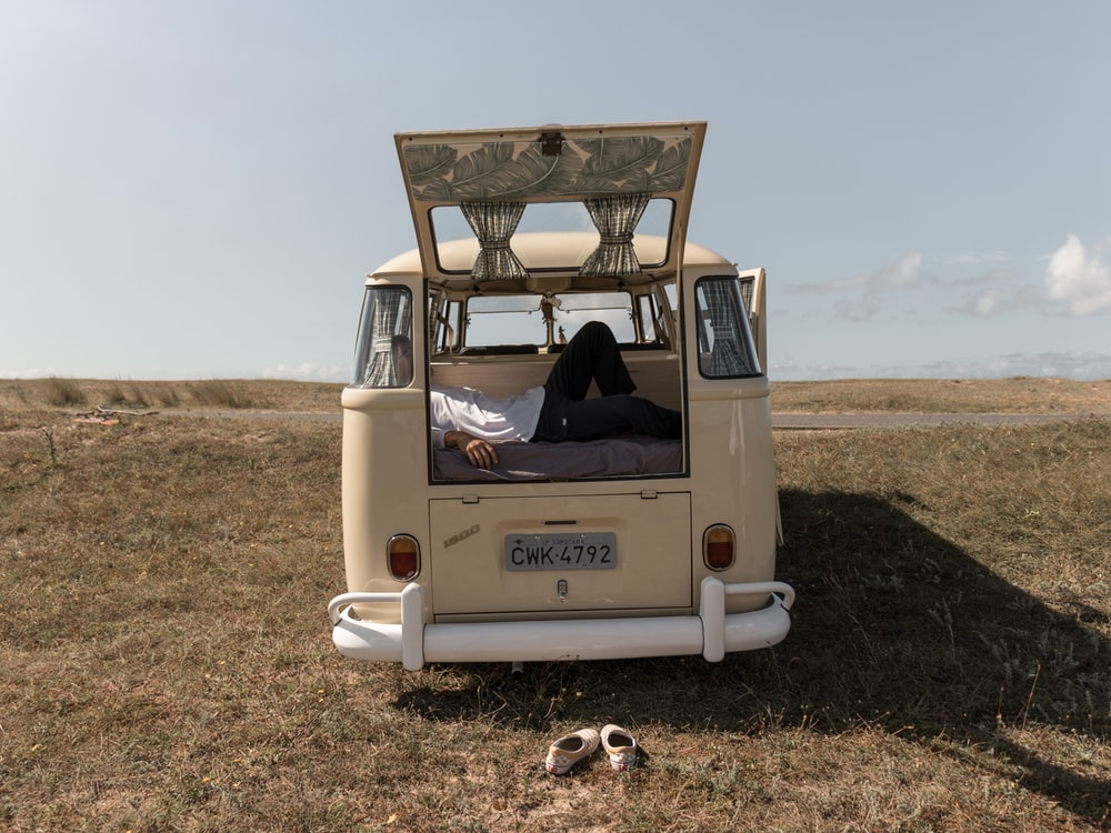 beige minivan parked in green grass field