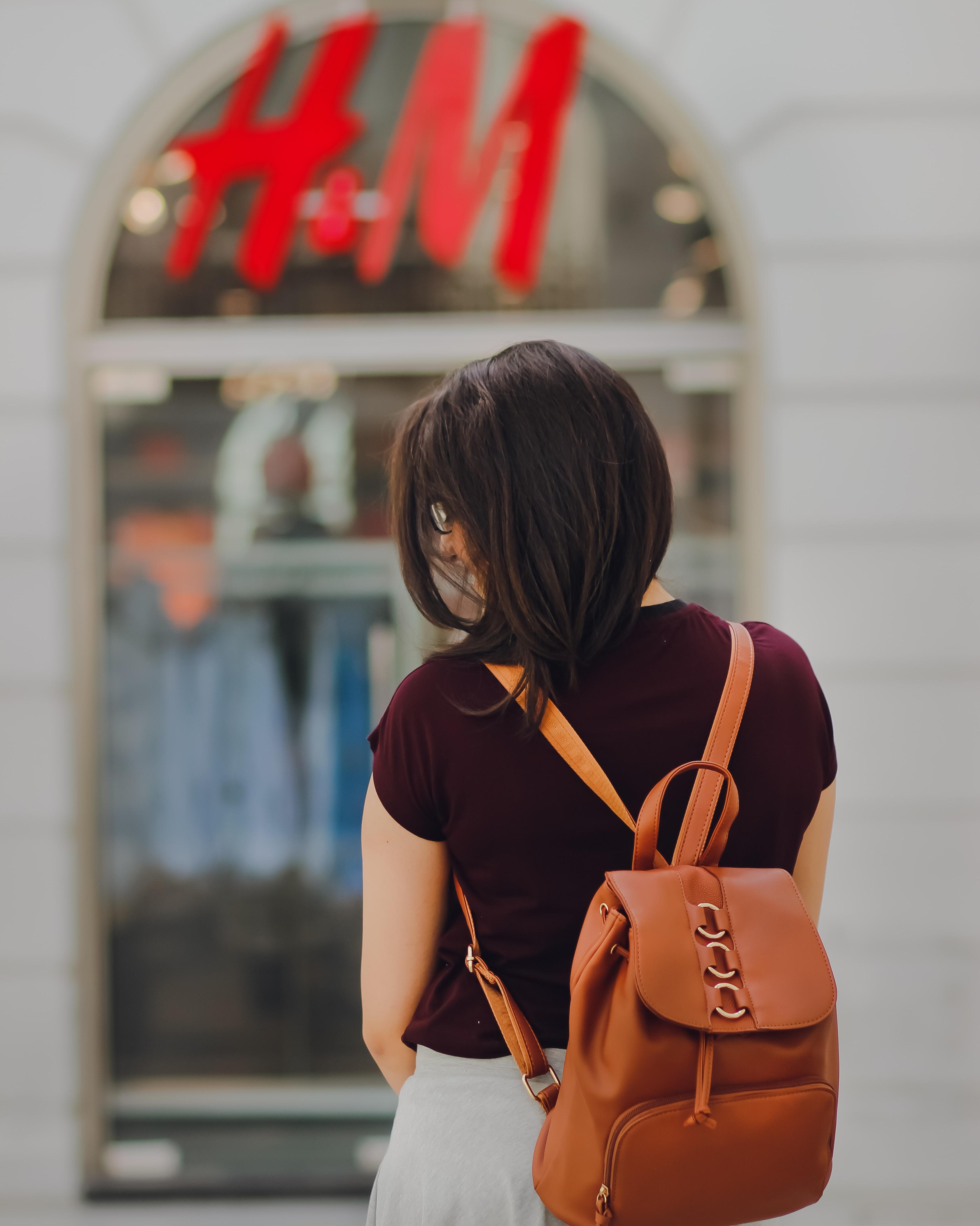 woman facing H&M store during daytime