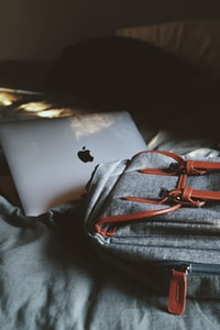 silver MacBook on bed
