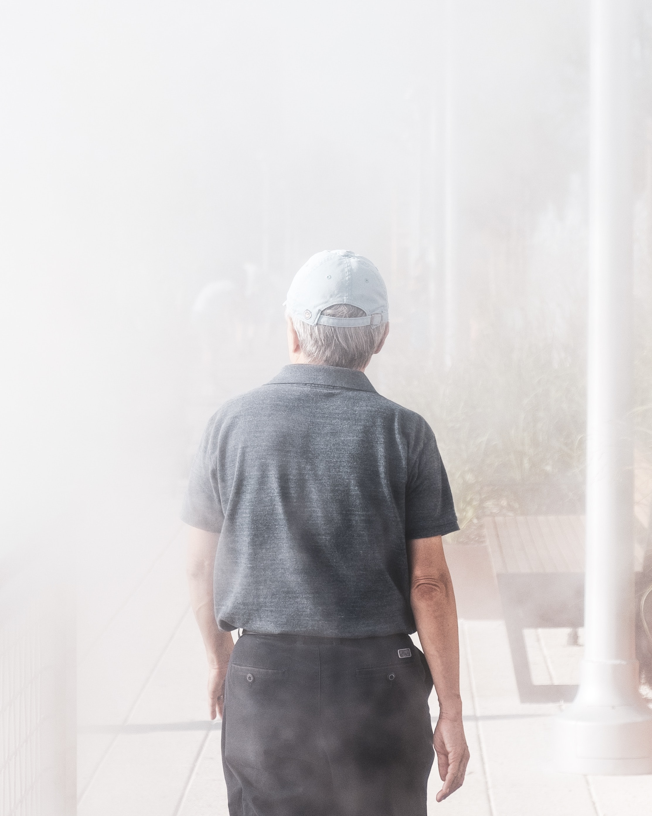 man walking towards smoke-covered building
