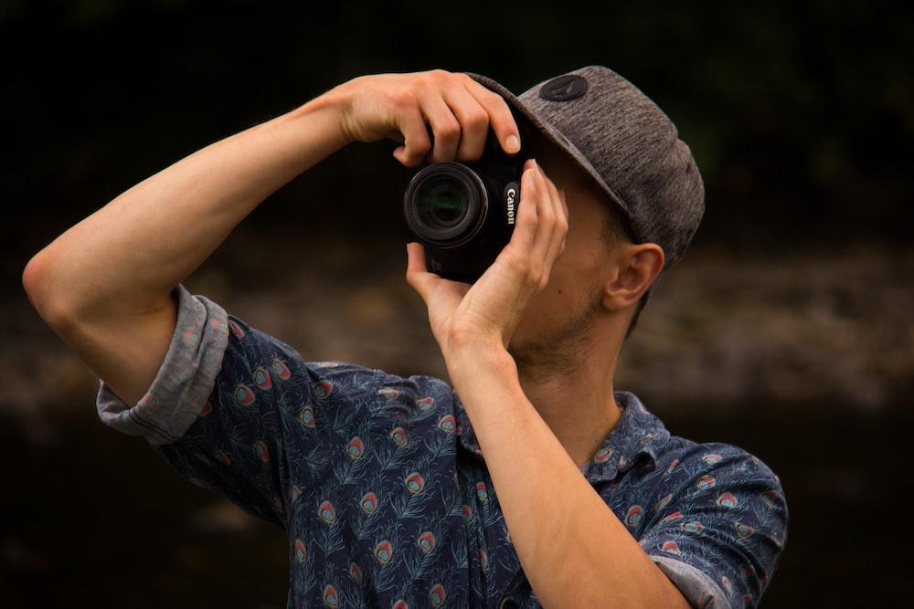 man holding canon camera taking photo