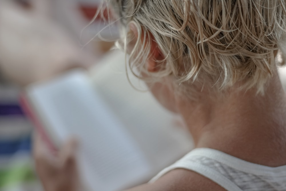 person in white tank top holding book
