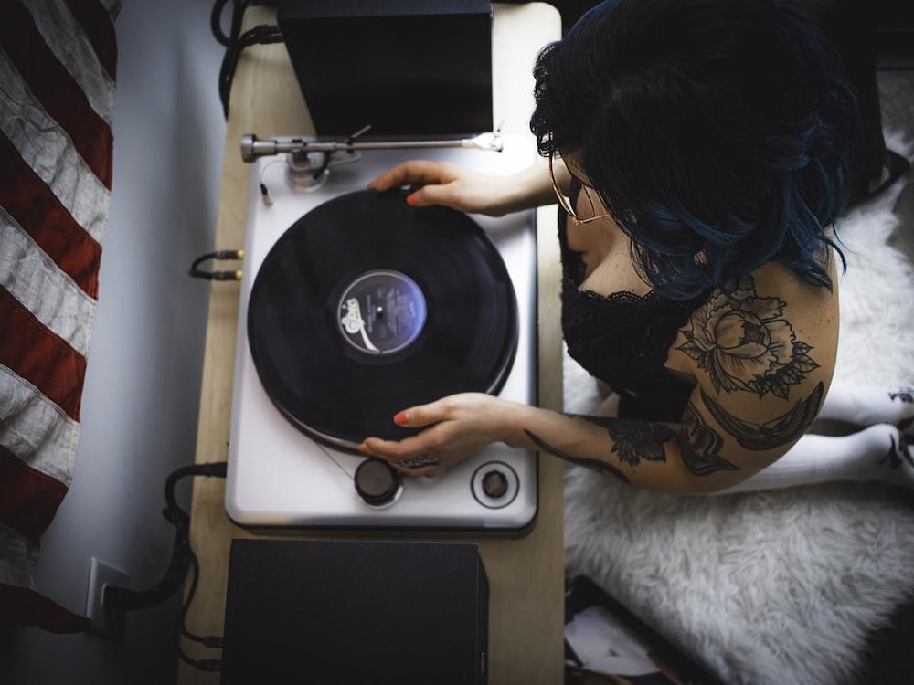 man holding black and gray vinyl player