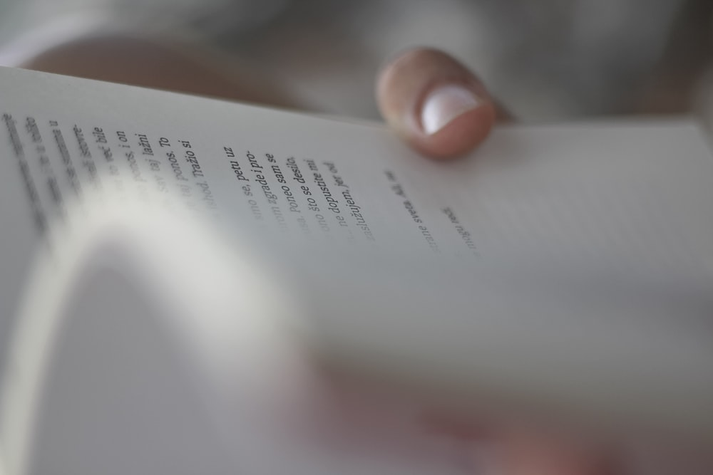 person holding white book