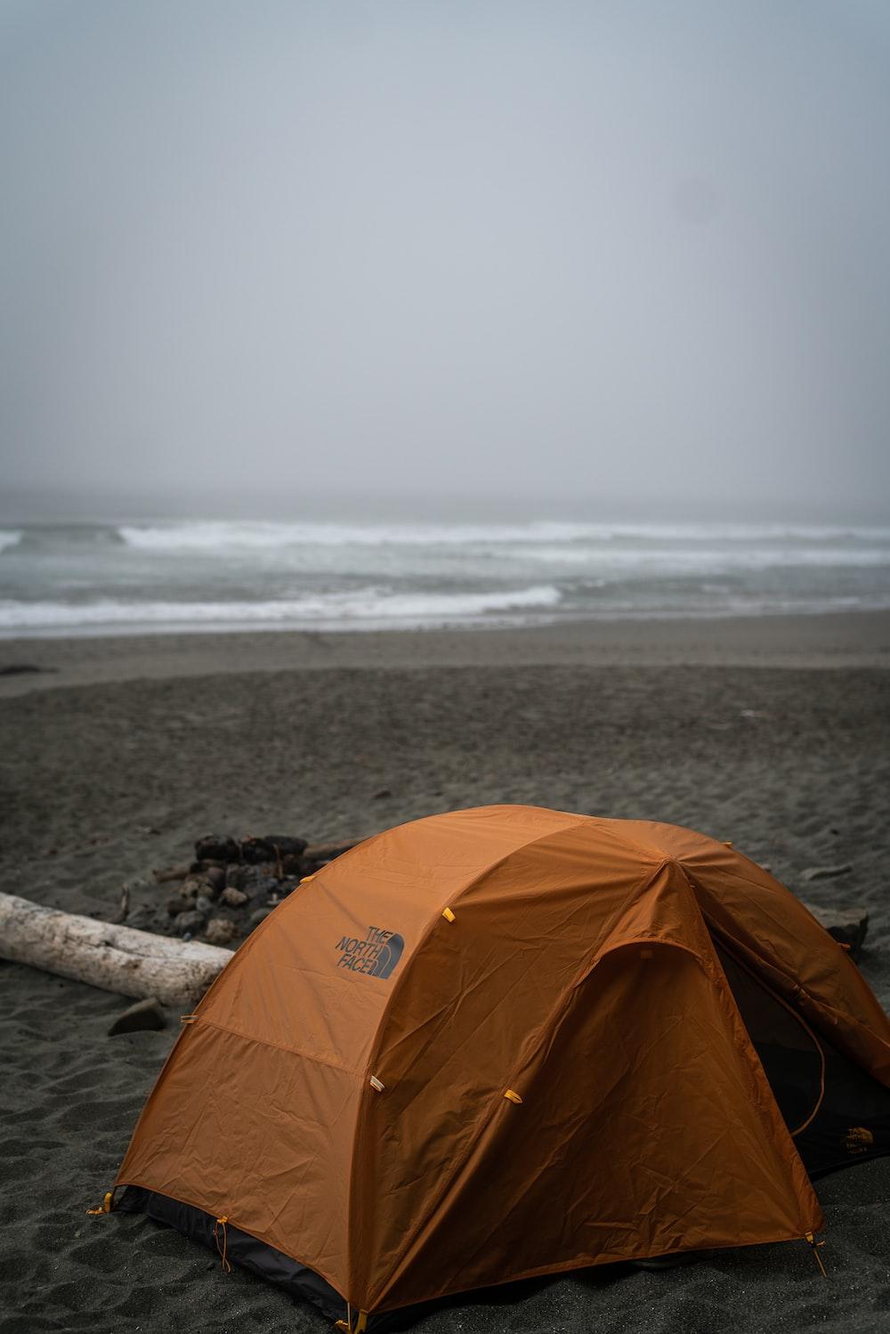 orange tent on sand near seashore