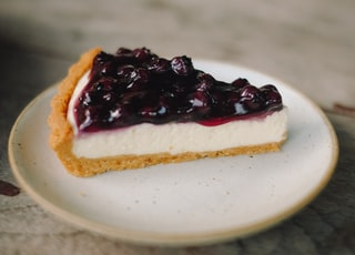 slice blueberry cheesecake pie on white ceramic plate