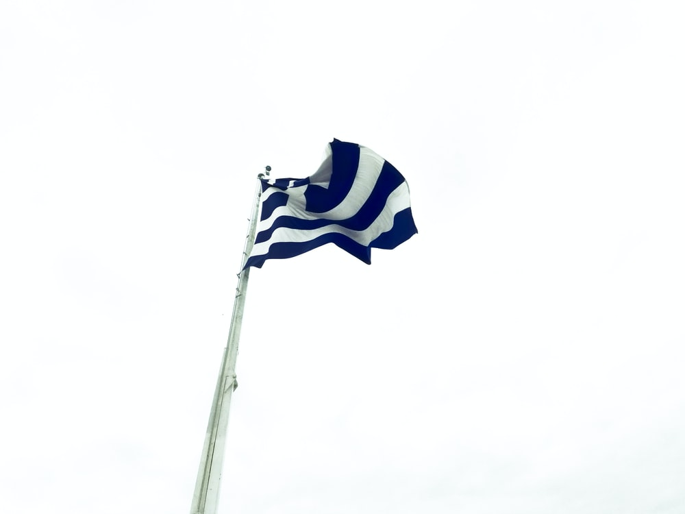 low angle photography of white and blue flag waving