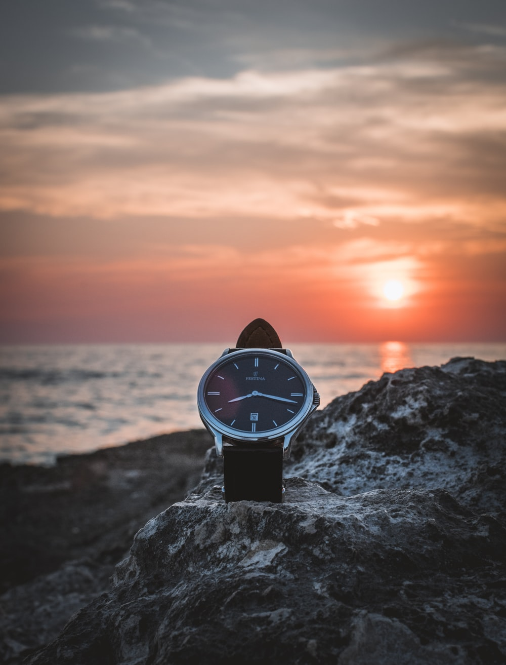 round silver-colored watch on rack during sunset