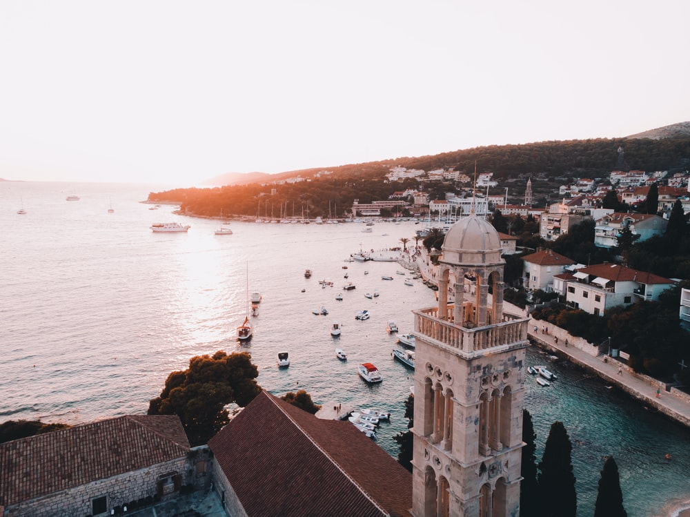 aerial photography of houses and dome building near sea at golden hour