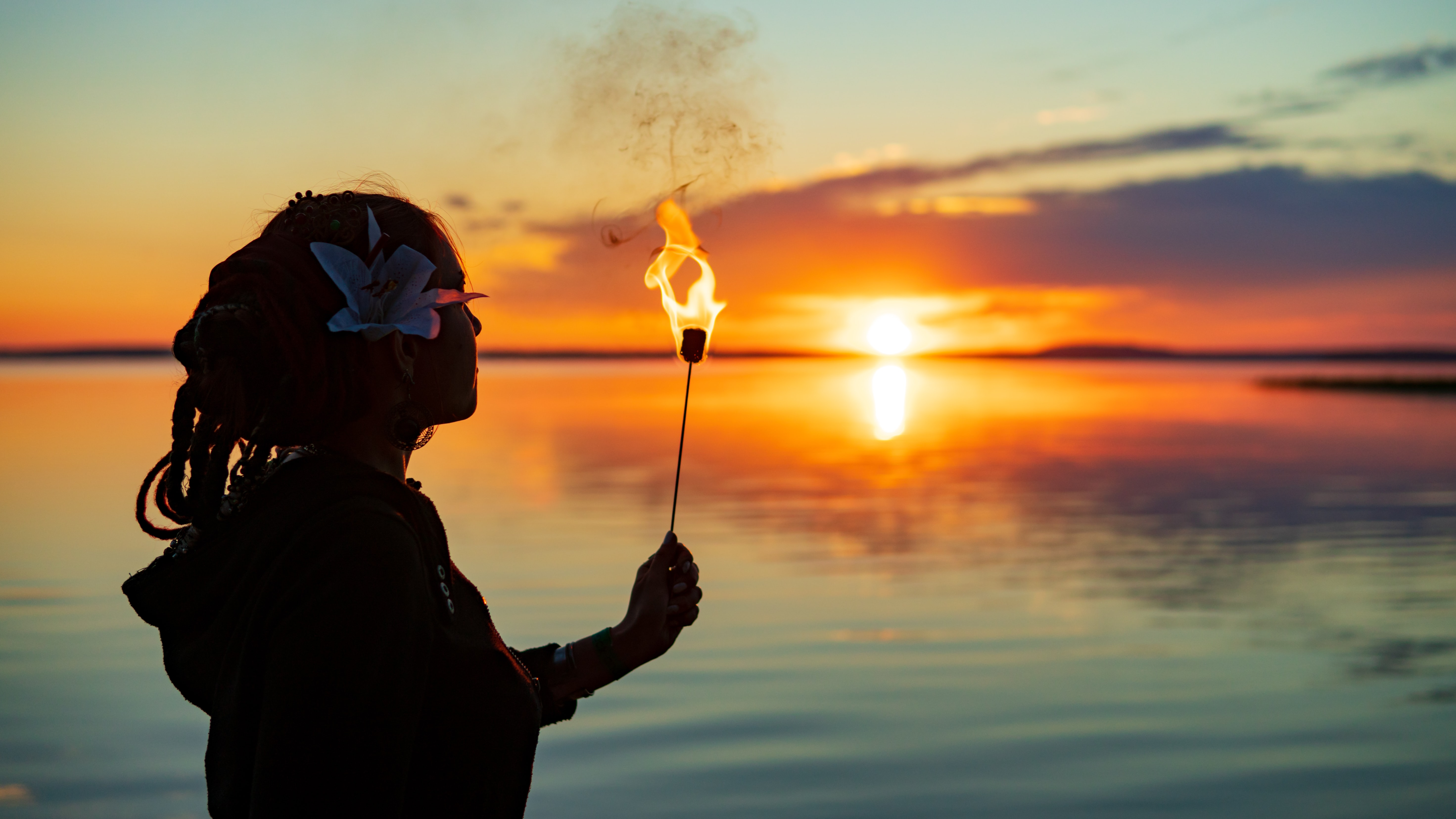 woman holding torch near body of water