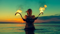 woman holding sickles with fire