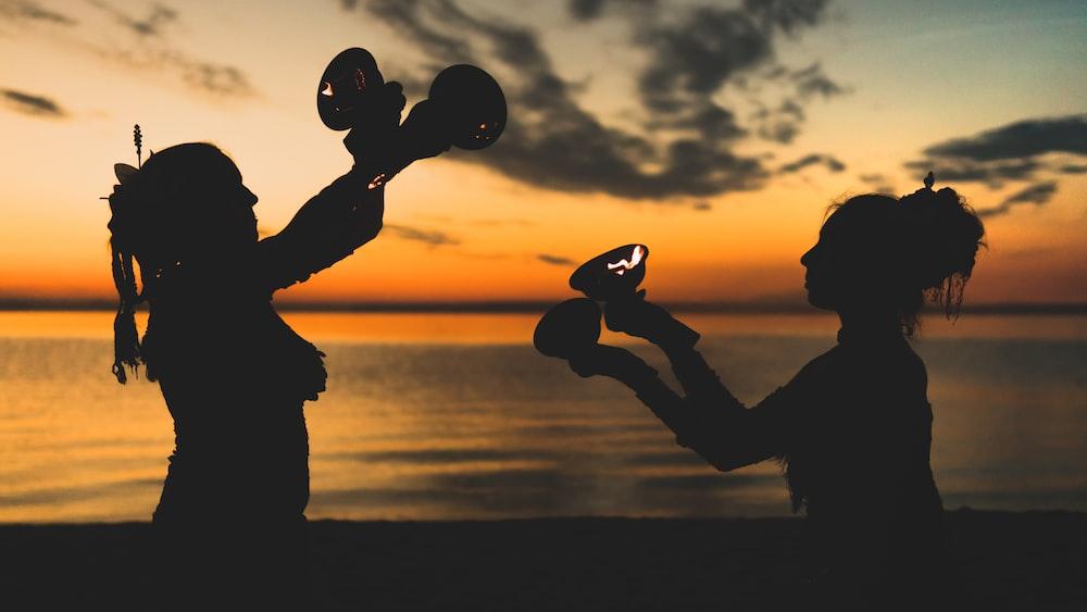 two women's silhouette near beach