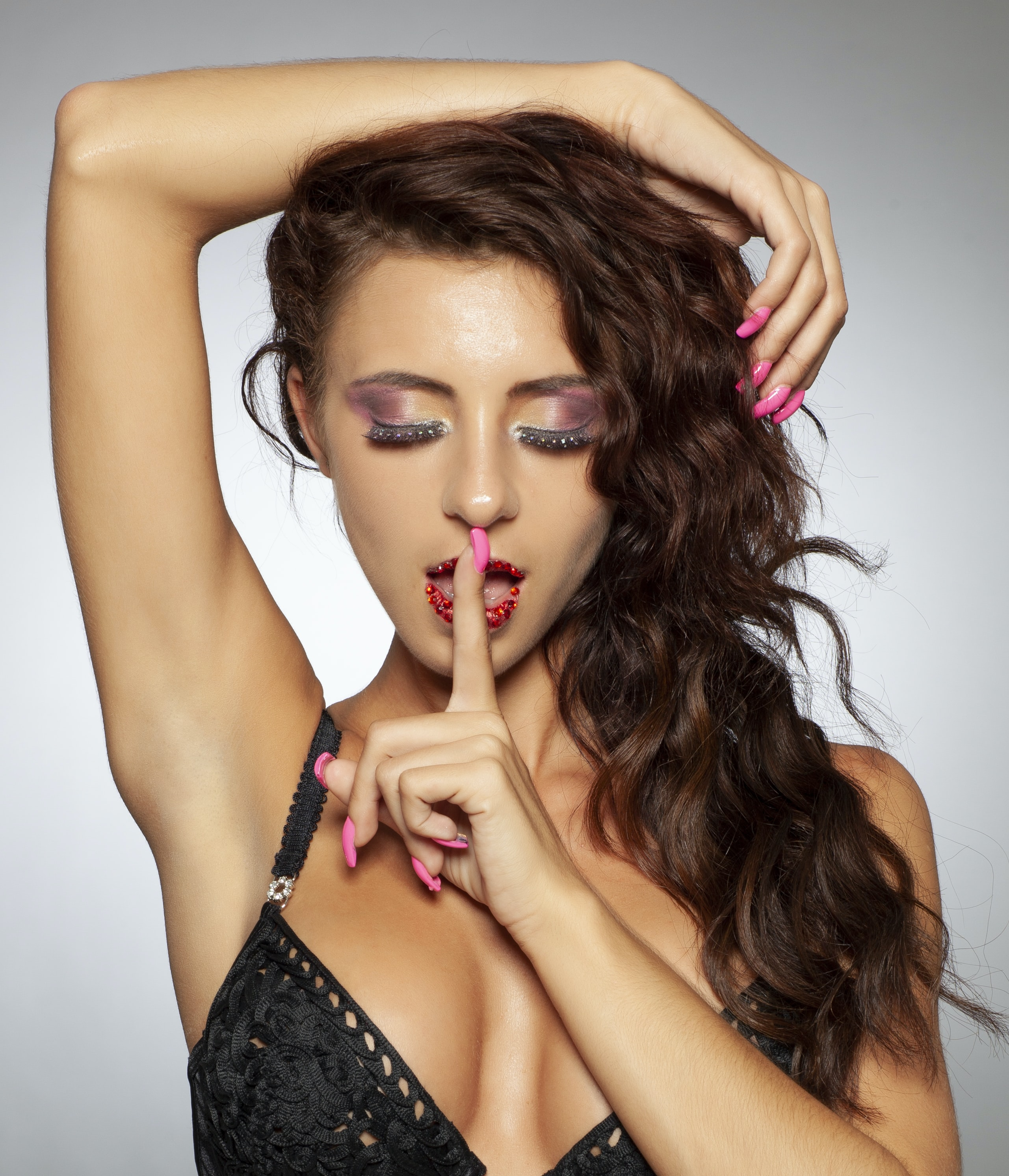 woman wearing black bra place right finger in her open mouth while left hand place on her head