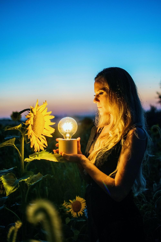 woman holding light bulb near sunflower taken during sunset