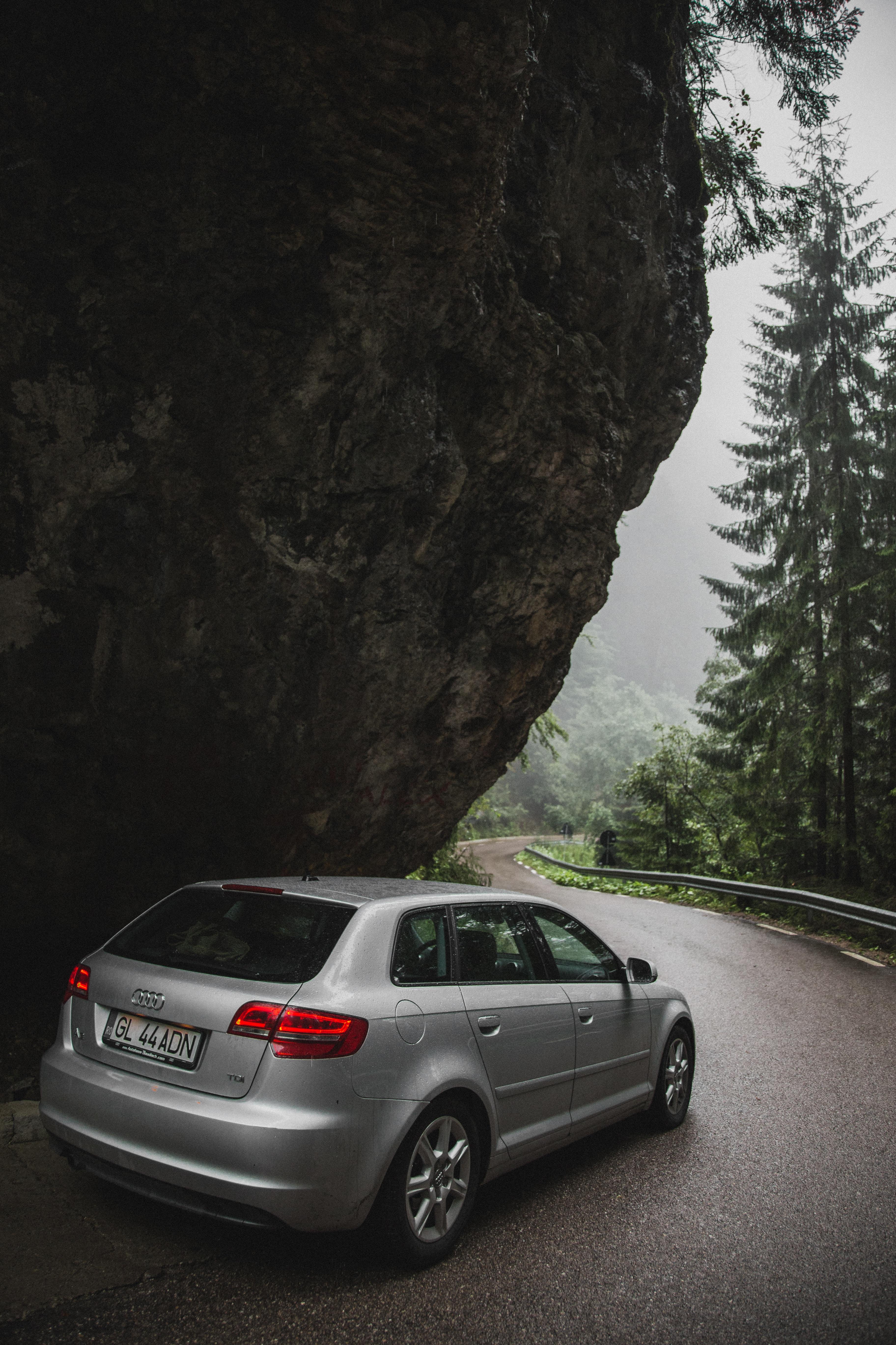 gray Audi 5-door hatchback passing on black rock formation