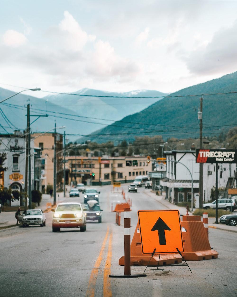 orange arrow road signage near car