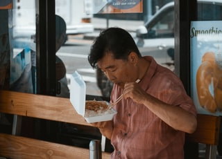 man sitting on brown wooden bench while eating