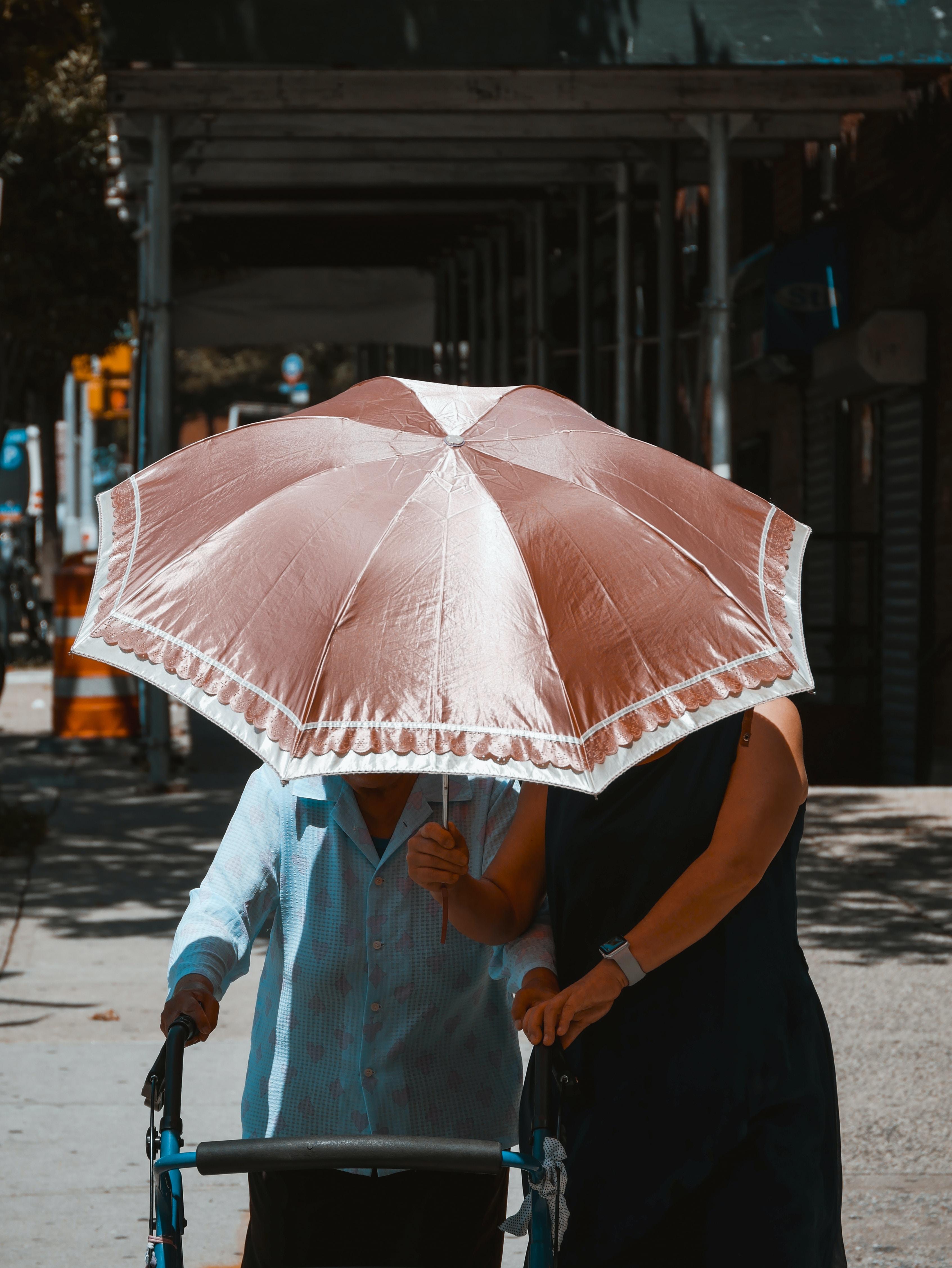 woman holding umbrella while walking