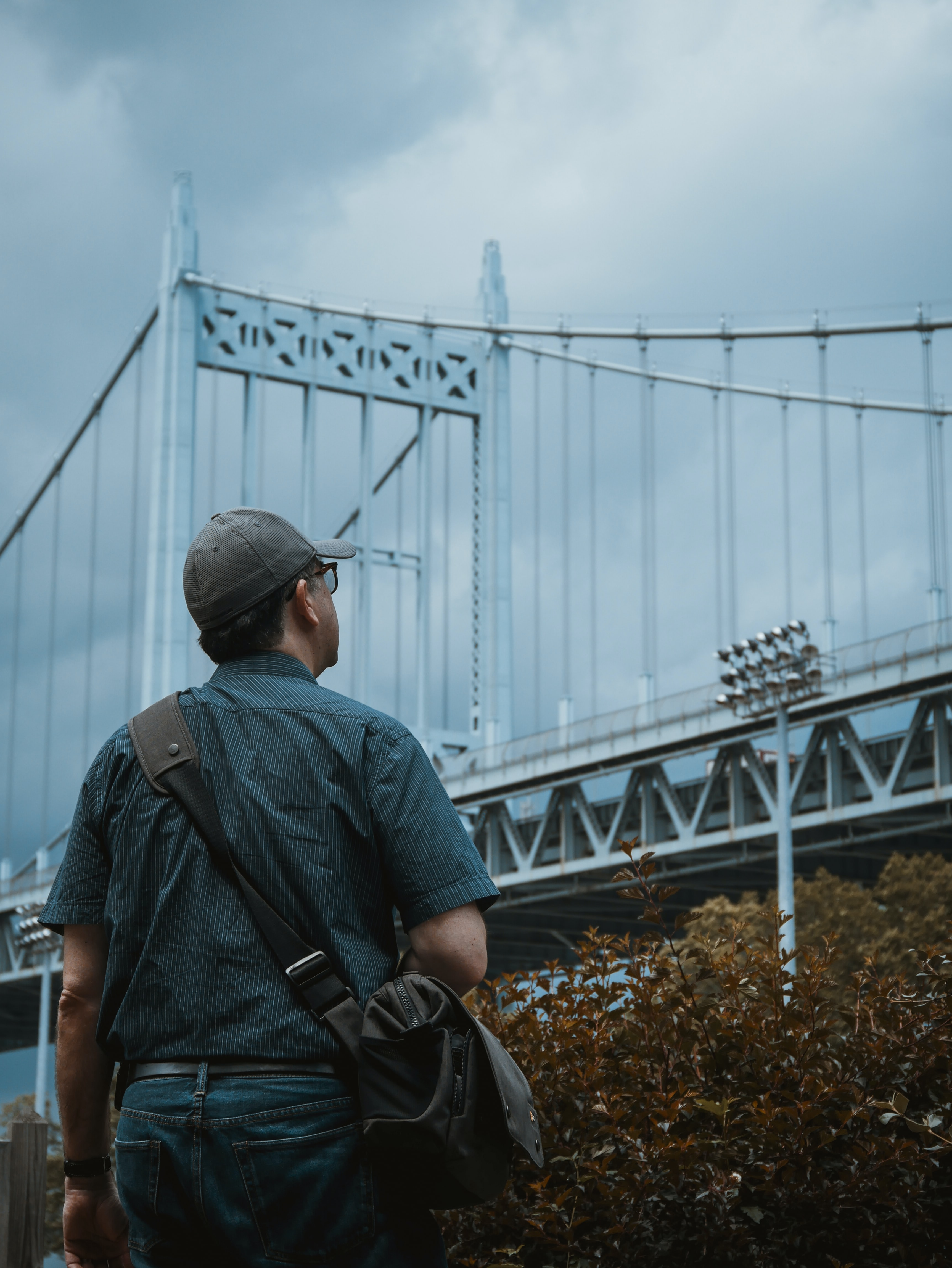 person standing and looking at gray metal bridge