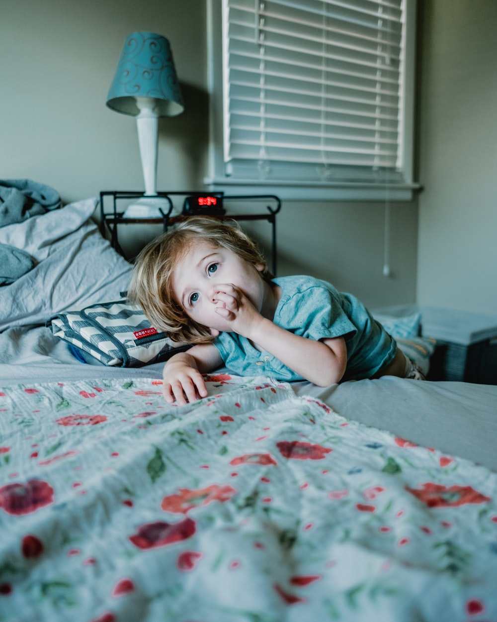 boy lying on bed while raising left hand near his mouth
