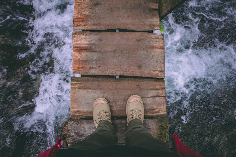 person standing on wooden bridge