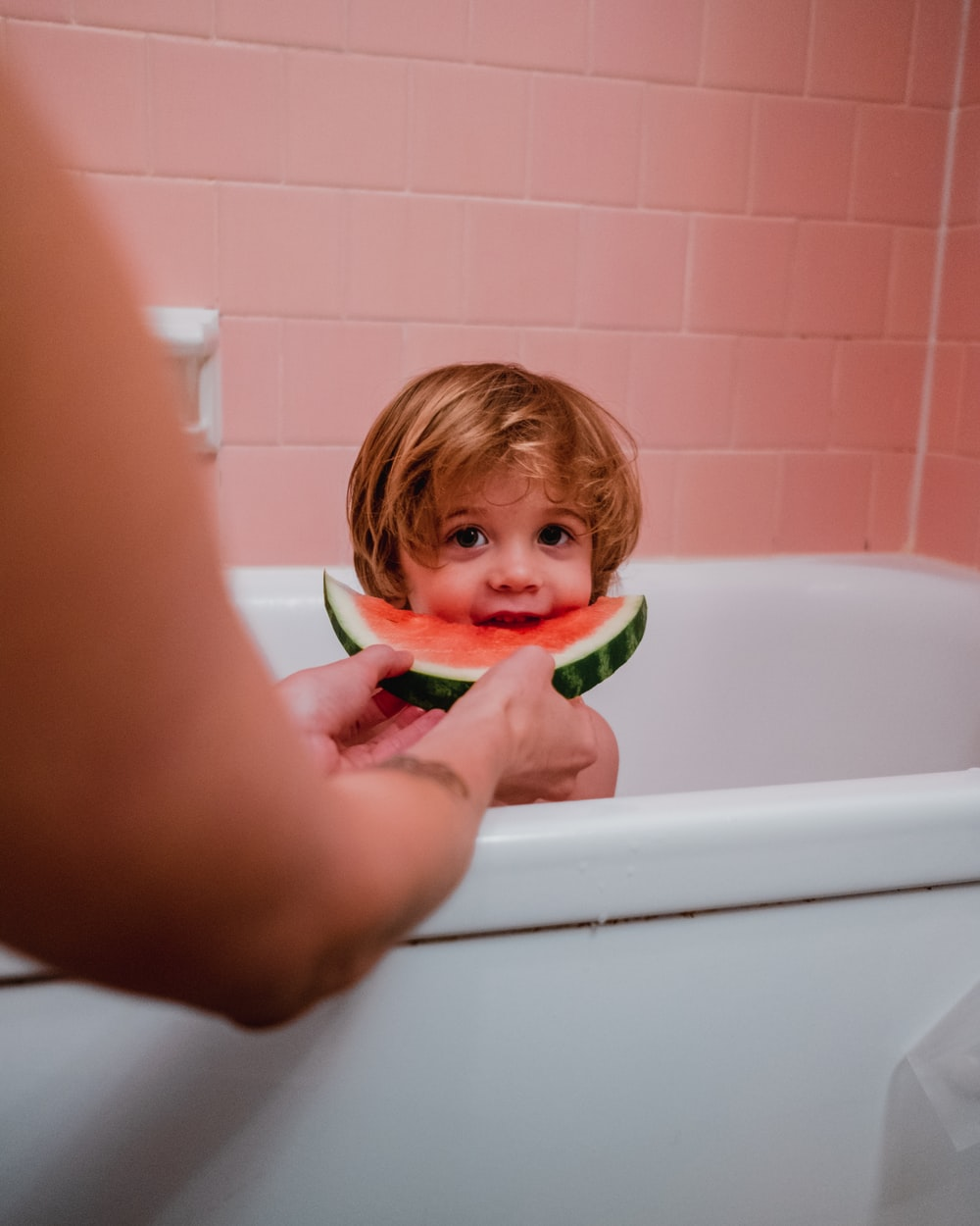 photo of boy in bathtub eating watermelon