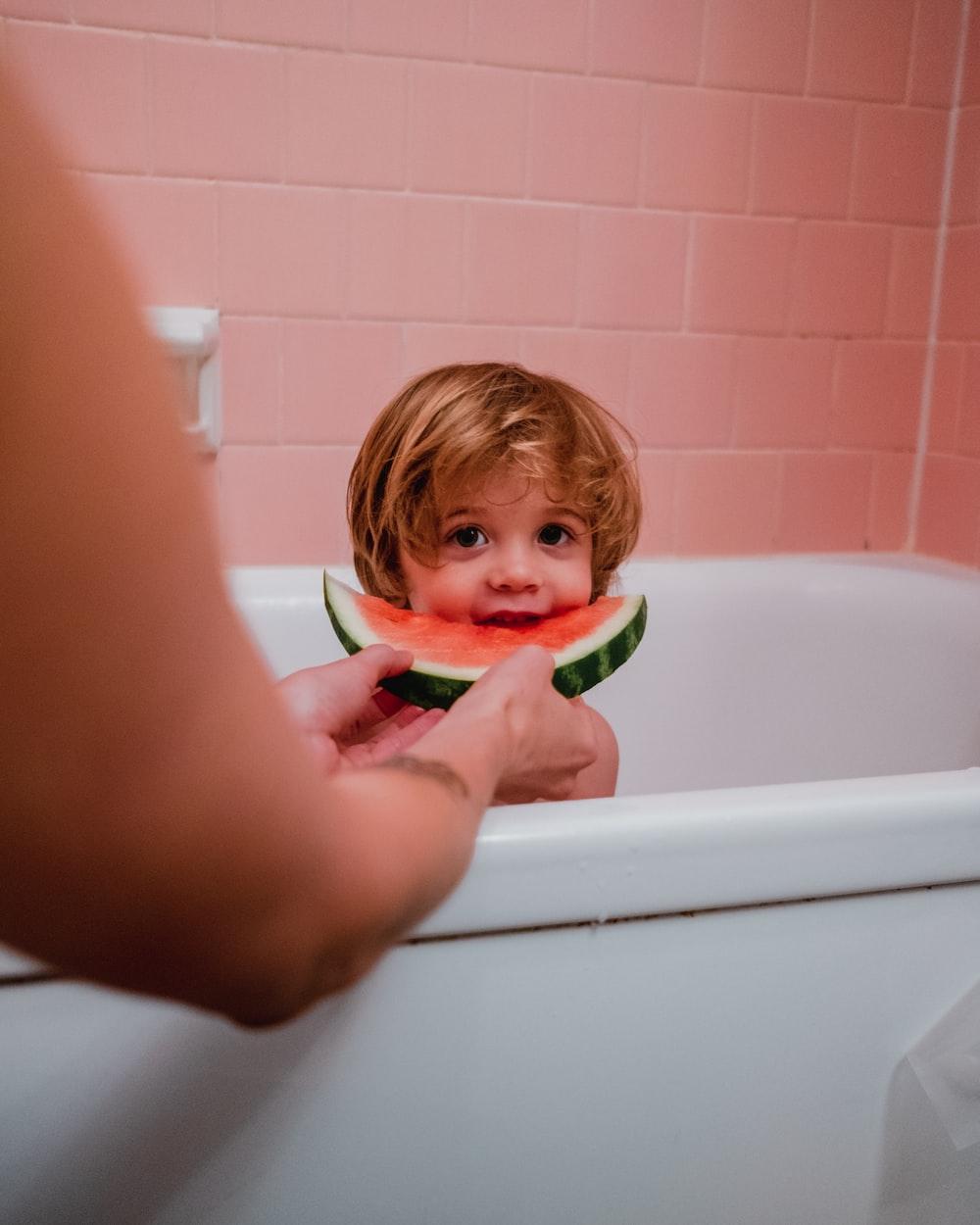 photo of boy in bathtub eating watermelon